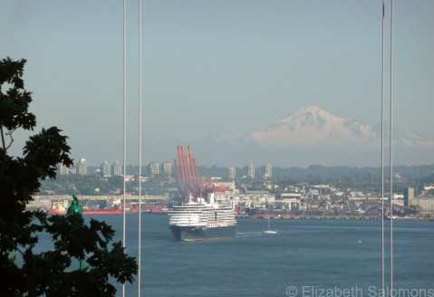A cruise ship sails out of Vancouver's Burrard Inlet, with Washington's Mount Baker in the distance.