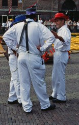 The cheese carriers wear the traditional costume: a white suit and a straw hat with a ribbon in the colour of their own group.